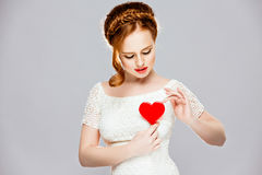 Very beautiful girl with red hair, in a braid holding a red Loll Royalty Free Stock Photo
