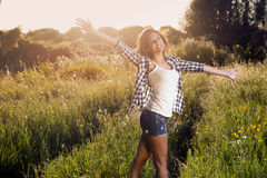 Very beautiful girl smiling in a field of flowers rejoicing Stock Photos