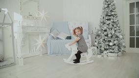 Very beautiful little girl riding on a wooden horse in the New Year`s room and smiling. Very beautiful little girl riding on a wooden horse in the New Year`s stock video footage
