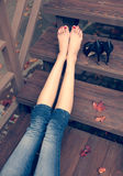 Very beautiful long legs, a girl is resting after a long walk sitting on the steps a warm autumn evening Royalty Free Stock Photo