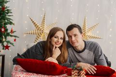 Very beautiful married couple on the bed in the New Year`s room. royalty free stock photography