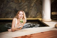 Model girl with blond hair in jacuzzi drinks green mojito Stock Images