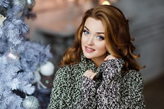 Very beautiful and sensual blonde girl in a knitted grey sweater. On the background of the Christmas tree, close up Royalty Free Stock Images