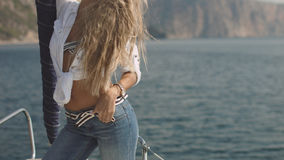 Very beautiful, sensual sexy blonde girl on the yacht. Very beautiful, sensual sexy blonde girl with blue eyes in jeans and white short blouse posing on the Royalty Free Stock Image