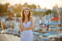 A very beautiful sensual and girl in a blue striped dress i. S walking on the background of yachts and the sea in summer stock photos