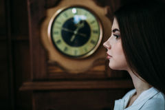 Very beautiful sexy brunette girl standing amid hours. Classical interior with the wall clock Royalty Free Stock Photo