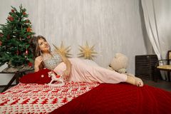 Very beautiful and woman in a pink dress in New Year`s decor, cradled in New Year`s style.
