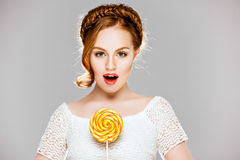 Very beautiful surprised girl with red hair, in a braid, holds r. Ound color candy, beauty in Studio on white background Royalty Free Stock Photography