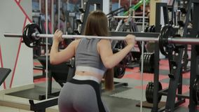 Very beautiful woman crouches with a barbell on her shoulders. stock footage