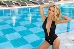 The very beautiful woman is standing in the sexy black swimsuit at the swimming pool. Very beautiful sexy blonde the long-haired woman is standing in the sexy Stock Images