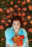 Very beautiful young brunette woman lies on the grass, her orange maple leaves on the park in autumn royalty free stock photography