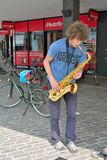 Very beautiful young man playing  the saxophone. GHENT, BELGIUM, 4 SEPTEMBER 2014: Very beautiful Unidentified young man playing  the saxophone in the streets Royalty Free Stock Image