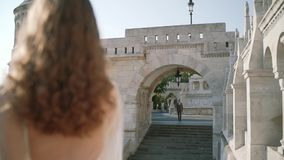 A very beautiful young woman or bride in a white dress, stay the balcony of the old castle, and looks at how the groom. Goes to her in the city Budapest stock video footage