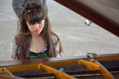 Very beautiful young woman playing  focused on the public piano. GHENT, BELGIUM, 4 SEPTEMBER 2014: Very beautiful Unidentified young woman playing  focused on Royalty Free Stock Photos