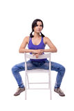 Very beautiful young woman with a tails is sitting on the chair legs wide apart isolated on white background Stock Photography