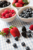 Very berry good!. Assortment of berries - raspberries, blackberries, strawberries & blueberries, some in bowls some not Royalty Free Stock Images