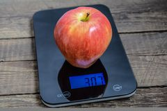 Very big apple on scales Royalty Free Stock Photography