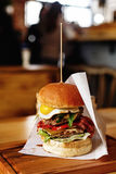 Very big juicy burger with vegetables meat cutlet and egg on woo Stock Photography