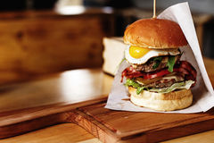 Very big juicy burger with vegetables meat cutlet and egg on woo Royalty Free Stock Photography