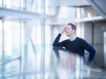 Thoughtful Man Standing At Office. In a very bright room, like a large office or an ariport terminal, a thoughtful man stands, strong reflection effect with Stock Images
