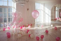 Very bright white room in a classic style. Lots of pink balloons, nobody. Luxurious living room with large window to the floor. The Palace is filled with pink Stock Images