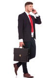 Very busy business man. Full length picture of a young business man walking with his briefcase and talking on the phone while looking away from the camera Royalty Free Stock Photo