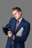 Very busy businessman. Talking on his cellphone while using his tablet Stock Image
