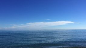 Very calm sea shore on sunny day. Panning to the left of a very calm sea shore in a sunny day stock footage