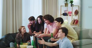 Very charismatic big company of friends are very excited enjoy the time together , while two of the friends playing on a stock video footage