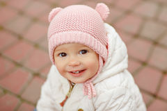 Very charming beautiful little girl with big brown eyes in a pin. K cap smiles in autumn, close-up royalty free stock photography