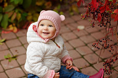 Very charming beautiful little girl with big brown eyes sitting, looking up and smiling on the background of red leaves of grapes stock photos