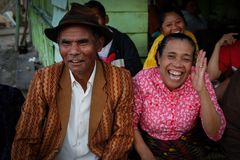 very cheerful laughing and fumbling Indonesian elderly woman in a pink blouse and her stylishly dressed man in a brown hat stock photo