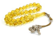 Very clean yellow Baltic amber rosary perspective view isolated on white. Very clean handmade yellow Baltic amber rosary beads with silver tassel isolated on stock images