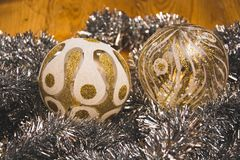 The very close and beautiful look on the two silver-golden glass Christmas balls. On the silver decorative chains royalty free stock images