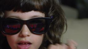 Female child as a rock star with sun glasses very close up FDV. Very close up portrait of a female child performing a rock star with sun glasses stock footage