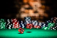 A very close up shot of 2 dice rolling on a green felt table top in very crisp focus, showing 4, 5 and 6 on the faces.  The stock image