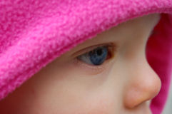 Very Close Up Side View of a Baby's Blue Eye. Very closeup shot from a side view of a Caucasian baby's blue eye, framed by a bright pink hat Stock Image