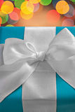 Very close up view on blue gift box with white ribbon on blurred Royalty Free Stock Images