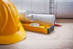 Very close up view on blueprints level and construction helmet Stock Image