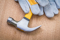 Very close up view on claw hammer and protective gloves on woode Royalty Free Stock Photo