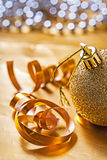 Very close up view on gold colored christmas bauble on table wit Royalty Free Stock Photos