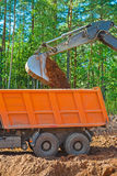 Very close up view on pouring ground from scoop of exkavator Stock Photography