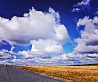 Very close up view on road and field with beauty cloudy sky inst Stock Images