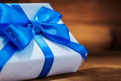 Very close up white giftbox with blue ribbon on vintage wood stock images