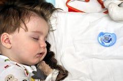 Very closeup portrait of the sleeping baby  with dummies nearbly. Very closeup portrait of the sleeping baby with dummies Stock Image
