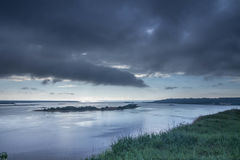 Very cloudy weather. Black clouds over the river. The edge of the river bank. Landscapes. Royalty Free Stock Image