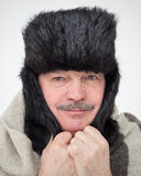 Very cold winter and unfavorable weather forecast. Elderly man bundled up in fur hat and warm scarf Royalty Free Stock Image