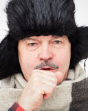 Very cold winter and unfavorable weather forecast. Elderly man suffering from a cough. Bundled up in fur hat and warm scarf Stock Photos