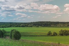 Colorful Bright Sunny Green Field Landscape With Blue Cloudy Sky, Trees And Hills stock images