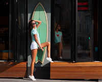 Very cool surfer tanned long-legged girl in white shorts and a turquoise shirt, white sneakers and sunglasses posing in the surf i Royalty Free Stock Images